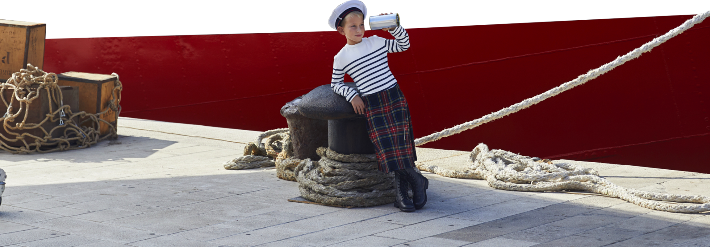 Visual of the new campaign with with a child in a kilt and striped shirt at quay holding a bottle of perfume like a long sight