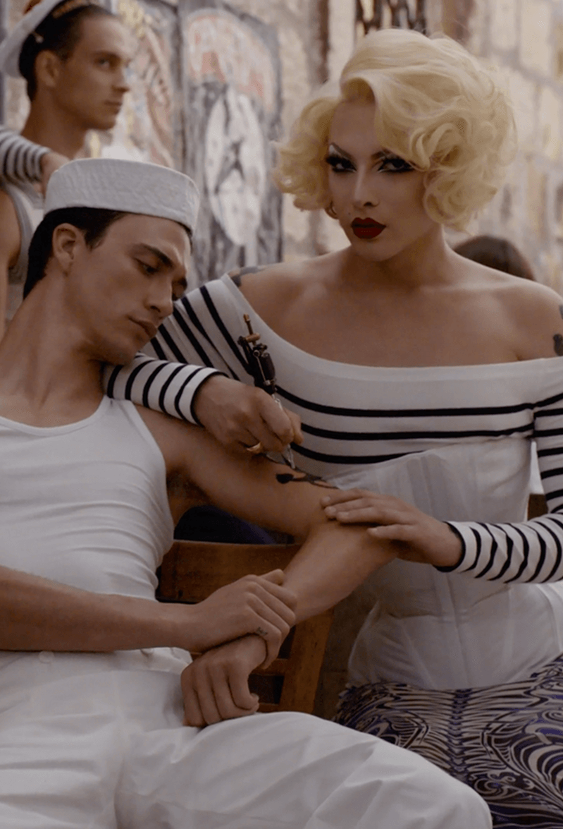 Visual of the new campaign with a woman tattooing a sailor and a mermaid wearing a captain's hat